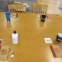 Table top with notebook, sticker, mugs and buttons.